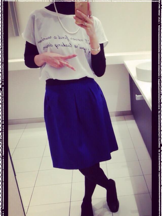 黒のタートルネックと白のTシャツを重ね着して、ブルーのスカートを合わせたコーディネート。