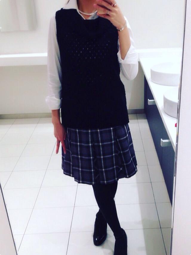 白シャツに黒のニットベスト、グレーを基調としたタータンチェックのスカートのコーディネート。