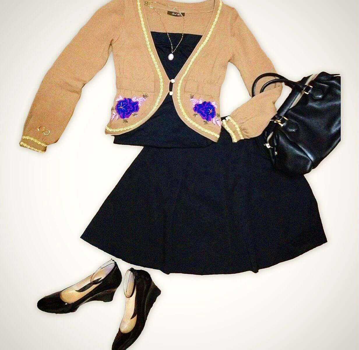 刺繍が入ったカーディガンとブラックのフレアスカートを合わせたコーディネート。