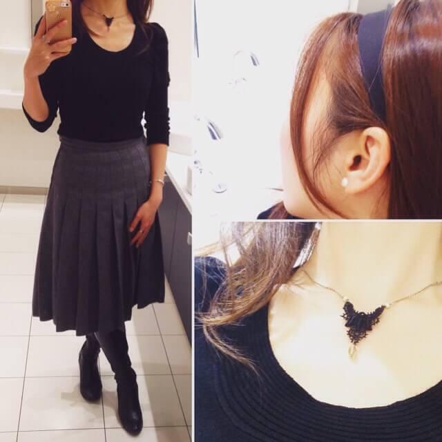 黒のパフスリーブニットとグレーのミモレ丈プリーツスカートのコーディネート。