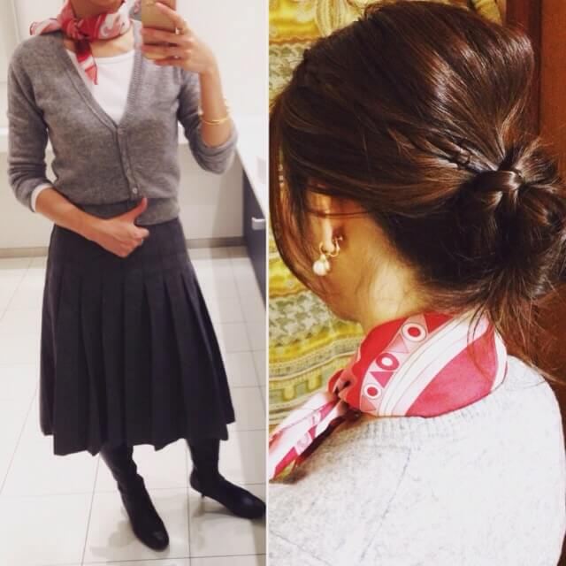 ピンク色のスカーフ、グレーのカーディガン、グレーのミモレ丈プリーツスカートのコーディネート。