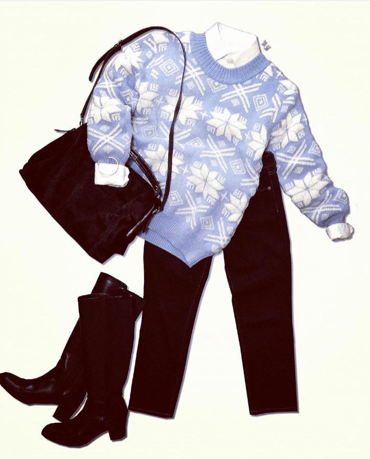 アイスブルーのニットと白シャツを重ね着し、黒のスキニーパンツを合わせたコーディネート。