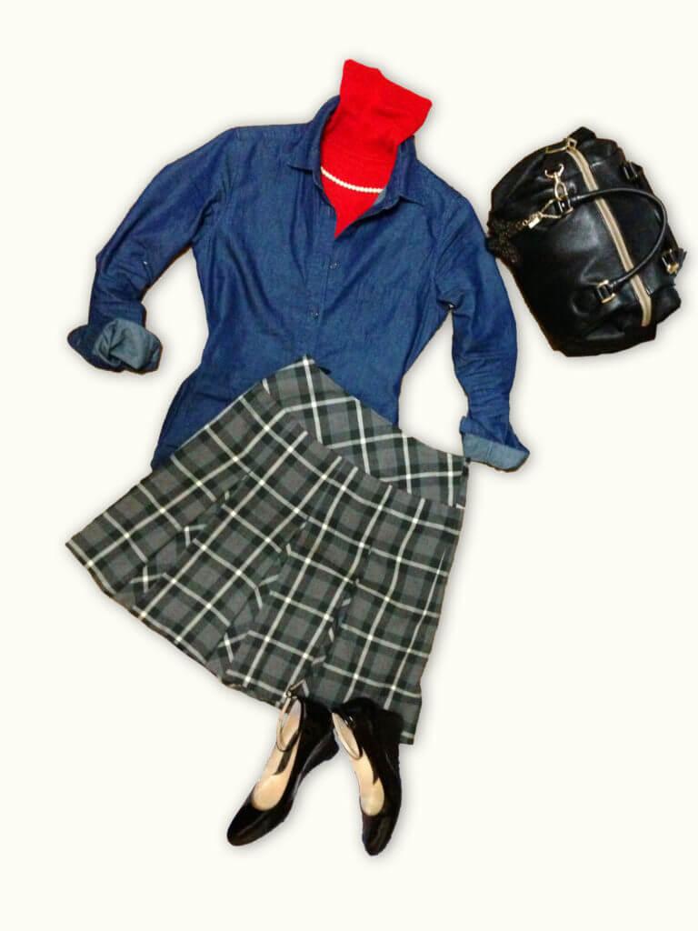 赤いタートルニットにデニムシャツ、グレー系チェックのスカートを合わせたコーディネート。