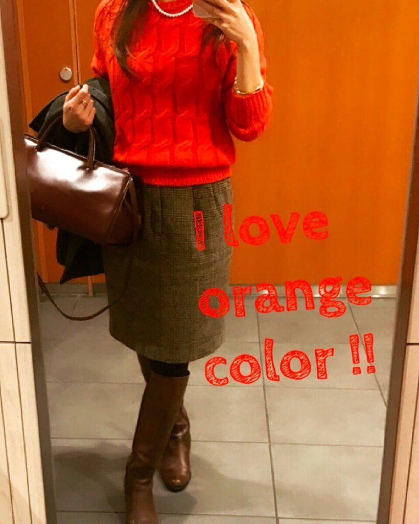 オレンジのぇーブルニットにチェックのブラウン系ライトスカートを合わせたコーディネート。