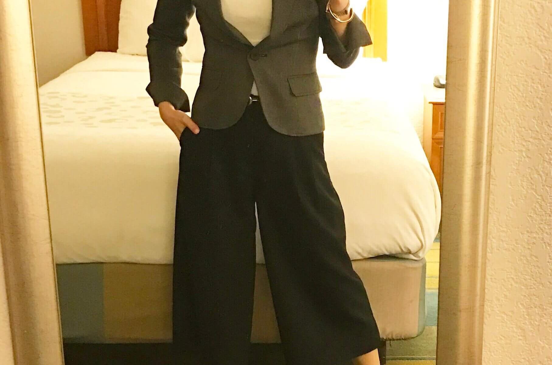 白のボートネックプルオーバーにグレーのジャケット、黒のガウチョパンツを合わせたコーディネート。